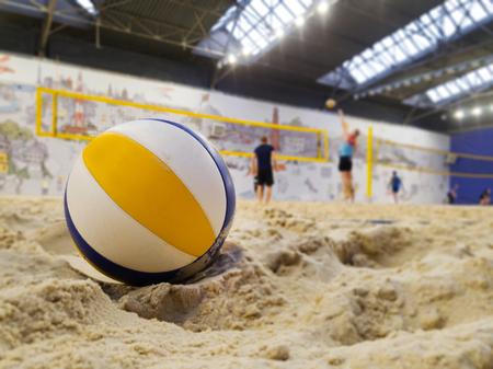 playing indoor beach volleyball closeup of ball in sands Reklamní fotografie