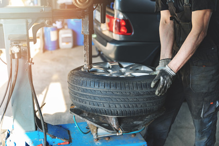 car mechanic changing tire on the rim in service garage