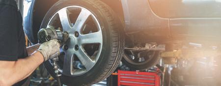Automechaniker schraubt das Rad in der Autowerkstatt