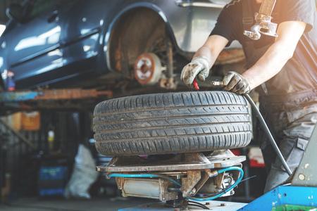 mechanic fixing tire at car repair service