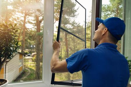 arbeider die het scherm van de klamboedraad op huisvenster installeert Stockfoto