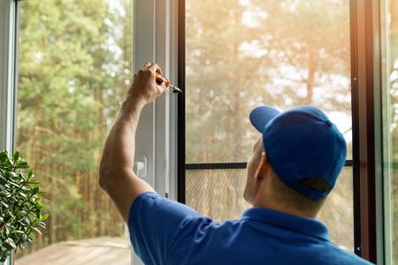 uomo che installa lo schermo del cavo della zanzariera sulla finestra di casa