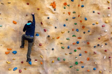 Bouldern - Mann klettert an künstlicher Felswand Standard-Bild