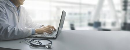 doctor working on laptop computer in modern clinics office. copy space