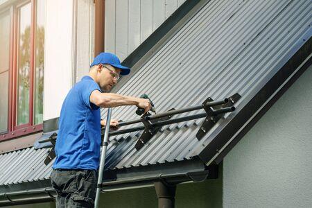 Couvreur installant un garde-neige sur un toit en métal