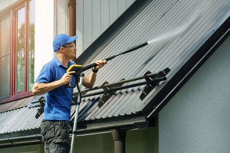 Hombre de pie en la escalera y la limpieza del techo metálico de la casa con hidrolimpiadora de alta presión Foto de archivo