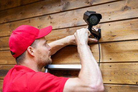 Sicherheitssystemtechniker installiert Überwachungskamera an Holzhauswand