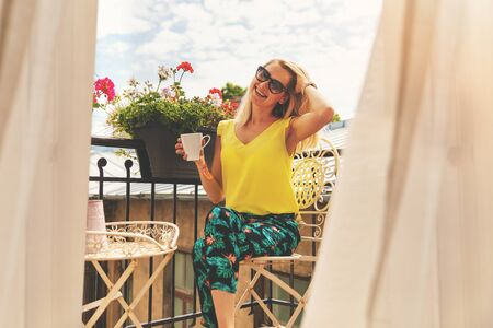 attractive smiling girl relaxing on balcony and having breakfast coffee