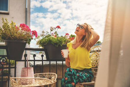 attractive young woman enjoying vacations and drinking coffee on hotel balcony Фото со стока - 130353586