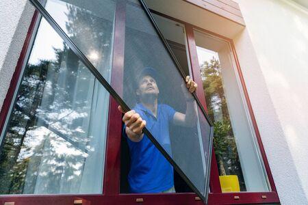 Trabajador que instala la pantalla de alambre de la mosquitera en la ventana de PVC de plástico