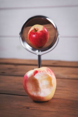 expectations and reality concept - bitten apple with perfect mirror reflection 免版税图像