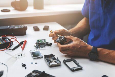 technician repairing broken digital camera lens in office