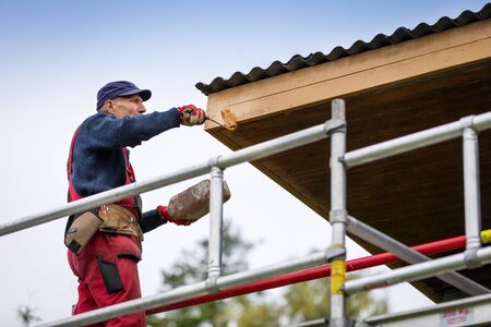 man on scaffolding painting house roof planks with paint roller