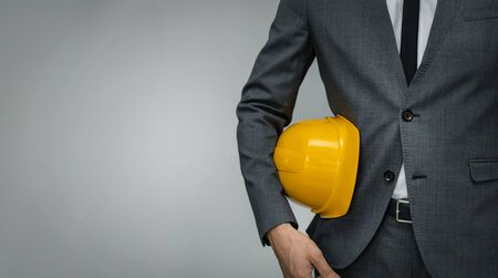 construction industry business - businessman holding yellow hard hat underarm on gray background with copy space Foto de archivo - 134609843