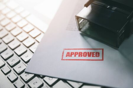 document with approved stamp on computer keyboard