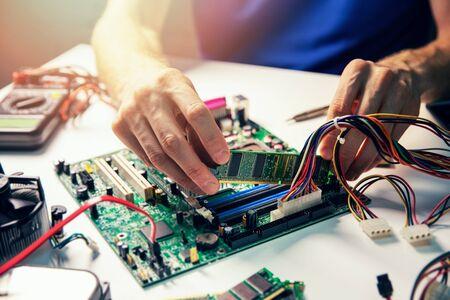 assemblaggio del computer - il tecnico installa il modulo di memoria ram sulla scheda madre