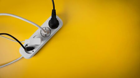 electricity consumption - electric extension cord full of power plugs on yellow background with copy space. top view