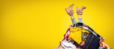 nogi kobiety ze stosu ubrań na żółtym tle z miejscem na kopię