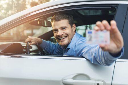 mężczyzna siedzący w samochodzie i pokazujący swoje prawo jazdy przez okno samochodu