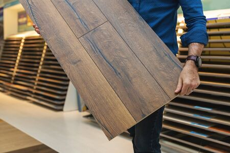 flooring store salesman with laminate floor sample panel in hands Standard-Bild