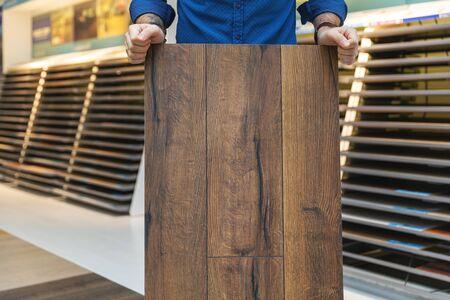 Bodenbelagsgeschäftsverkäufer mit Laminatbodenmusterplatte in den Händen