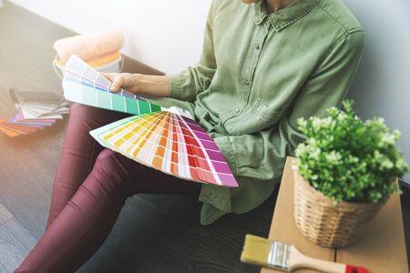 部屋の床に座って、新しいインテリアデザインのためのサンプルから塗料の色を選択する女性 写真素材