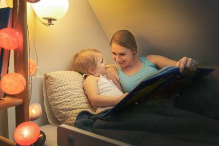 Mutter liest ihrem Kind am Abend vor dem Schlafen zu Hause ein Märchenbuch vor