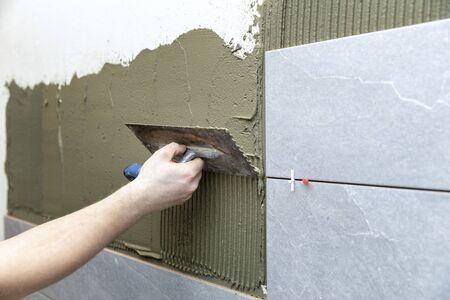 man apply tile adhesive on the bathroom wall