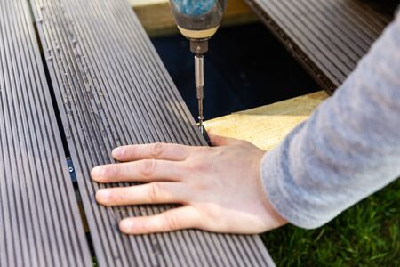 terrace deck construction - man installing wpc composite decking boards Stock Photo