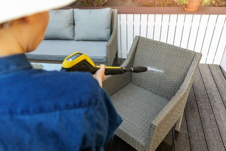 woman doing garden terrace furniture cleaning with high pressure washer
