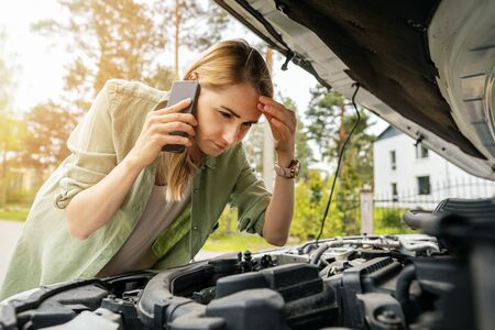 woman looking at broken car engine and talking on the phone Archivio Fotografico