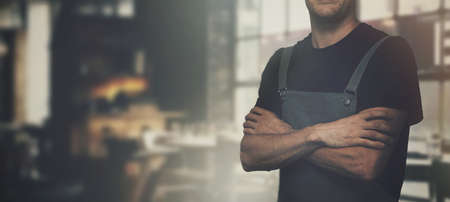 barista standing in coffee shop with arms crossed. copy space