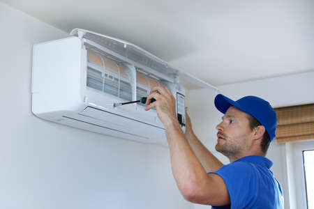 hvac services - technician installing air conditioner on the wall at home