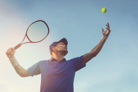 active young man playing tennis outdoors. serve the ball against blue sky