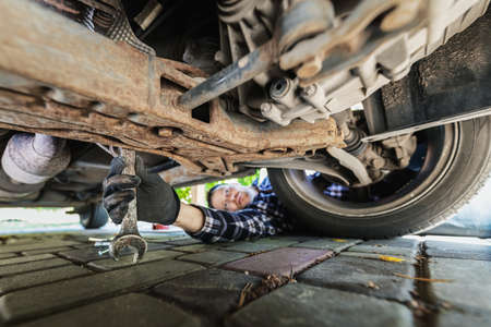 man repairing car. mechanic inspecting suspension system under the vehicle at home garage