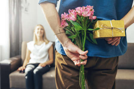 husband hiding romantic surprise present and flowers behind back to beloved wife at home