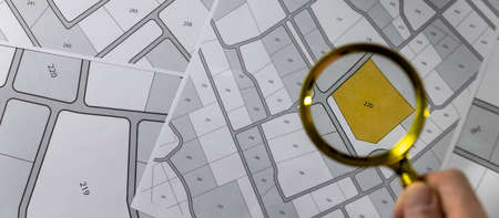 hand with magnifier on cadastre map - search and buy land concept. banner copy space