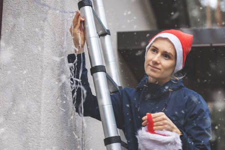 woman with santa hat standing on ladder outdoors and installing christmas lights and decors on house facade