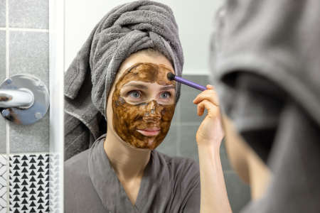 woman applying mud facial mask with brush in front of mirror in bathroom at home. skin care beauty treatment