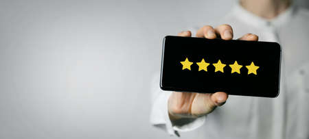 excellent service and customer feedback. woman holding phone with 5 star rating on screen. copy space