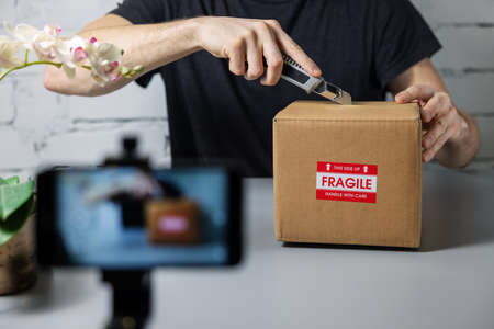 man recording unboxing video with mobile phone. cutting cardboard box with knife. social media marketing