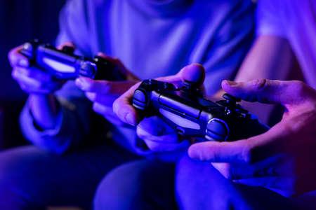 friends playing console video games. controller in hands closeup. neon lights Standard-Bild