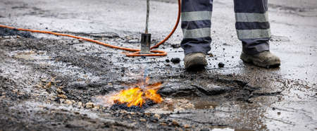 road worker prepare pothole with gas torch flame for repairing. copy space Standard-Bild