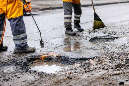 pothole repair - maintenance service workers working on the road Standard-Bild