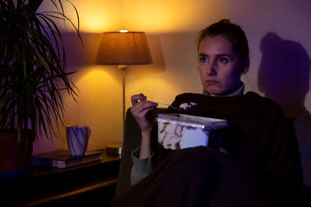 lonely sad woman eating ice cream from container while sitting on couch and watching tv at home