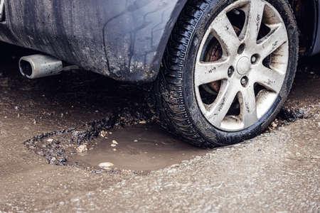 car tire in big pothole on the road Standard-Bild