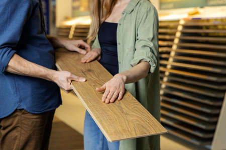young couple choosing laminate floor design together for new house interior in flooring store