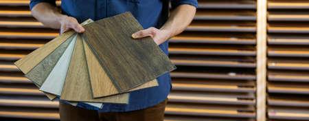 flooring store seller with vinyl floor samples in hands. copy space Standard-Bild
