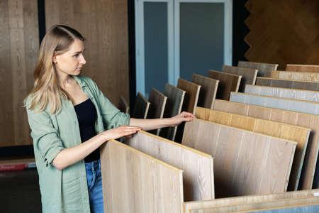 woman choosing laminate floor design from samples in flooring store