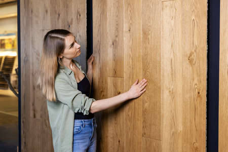 young woman choosing materials for her new home at interior design store